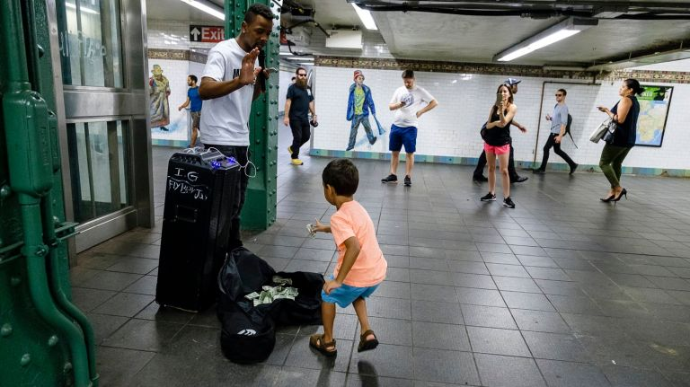 Gerald Graham greets a child while performing in the subway at West 42nd Street on Aug. 16.