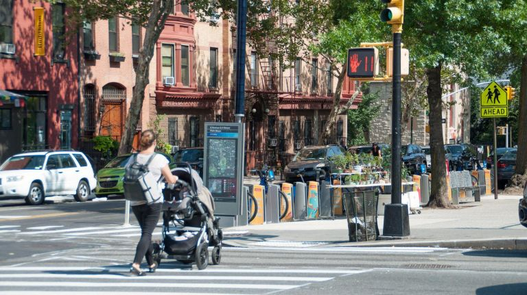 A woman walks with a stroller at an intersection along the Ninth Street corridor as the city Department of Transportation nears the completion of its street redesign.