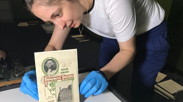 Collections manager Lisa Goulet puts the finishing touches on a pamphlet that was published to commemorate the grand opening of Fraunces Tavern as a restaurant and museum in 1907.