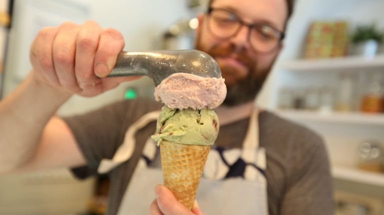 Sugar Hill Creamery co-owner Nick Larsen scoops strawberry-basil and blackberry-pistachio flavors.