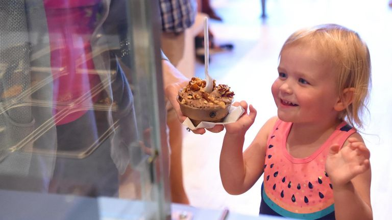 Madeline McCormick, 3, reaches for her ice cream from her mom, Jess McCormick, at Four Winters.