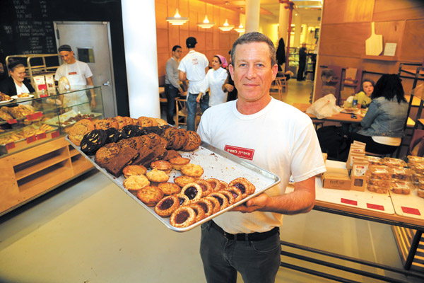 Photo by Jefferson Siegel Master baker Uri Scheft with a tray of tantalizing treats at Breads Bakery.