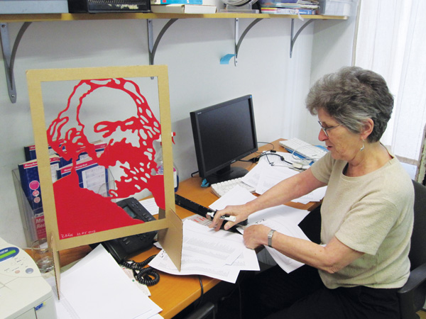 Liz Mestres, Brecht Forum's outgoing executive director, working in her office at 451 West St. under the watchful gaze of Karl Marx.