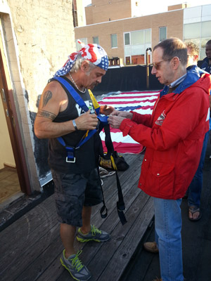 Photos by Heather Dubin John Casalinuovo put on a harness to prepare to drop the 1,800-square-foot flag over the building's side.
