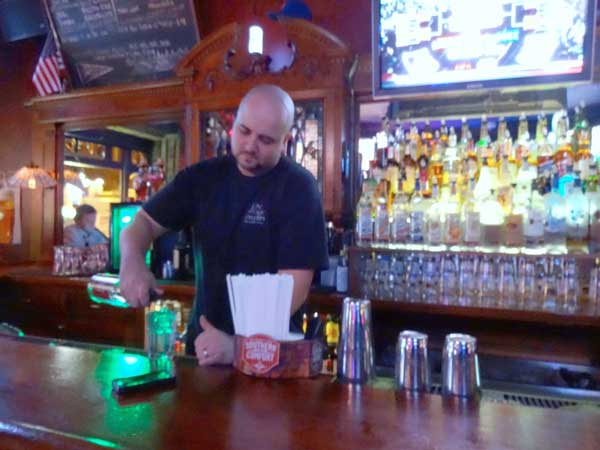 Brendan Kirkpatrick, head bartender at The Village Tavern, poured a drink next to a patron's phone left carelessly on the bar top. Photo by Paul Bufano