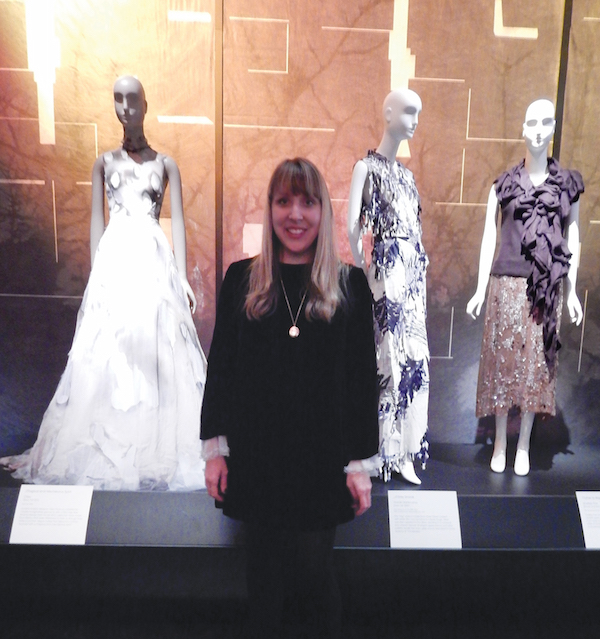 """Colleen Hill, associate curator of costume, standing in front of the """"Cinderella"""" installation, one of her favorites from the exhibit. Photo by Lindsay Bu."""