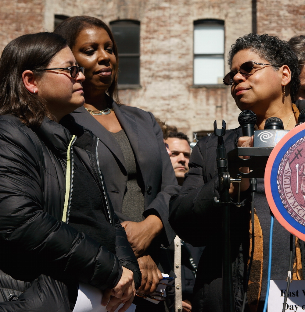 """At the Day of Remembrance ceremony, Mildred Guy, a displaced tenant from the former 119 Second Ave., spoke about the apartment her family used to call """"Mommy's Home,"""" as from left, Councilmember Rosie Mendez and Public Advocate Letitia James listened.  Photo by Patrick J. Eves"""